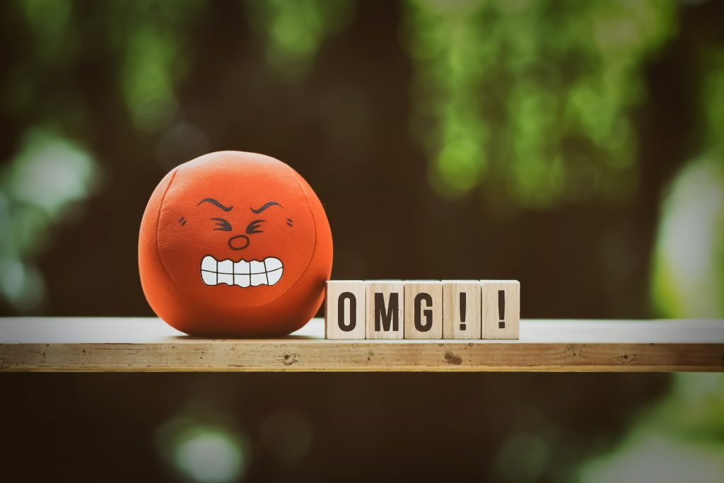 angry emoji ball with letter blocks spelling omg