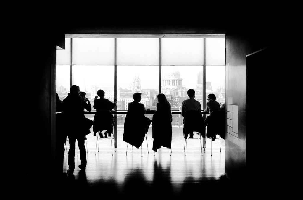 Silhouettes of people sitting in a bright room, with their backs to the camera
