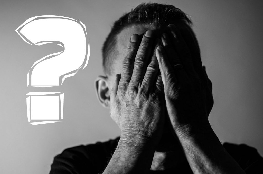 Man doing a facepalm with both hands next to a question mark
